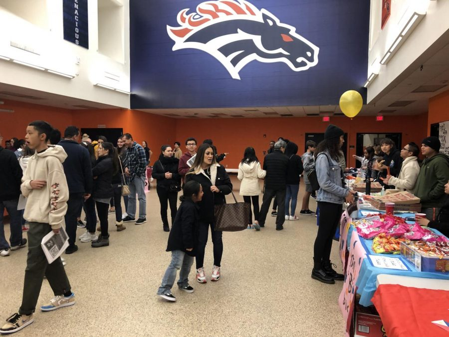 8th grade parent night. Students and parents visiting different club booths.